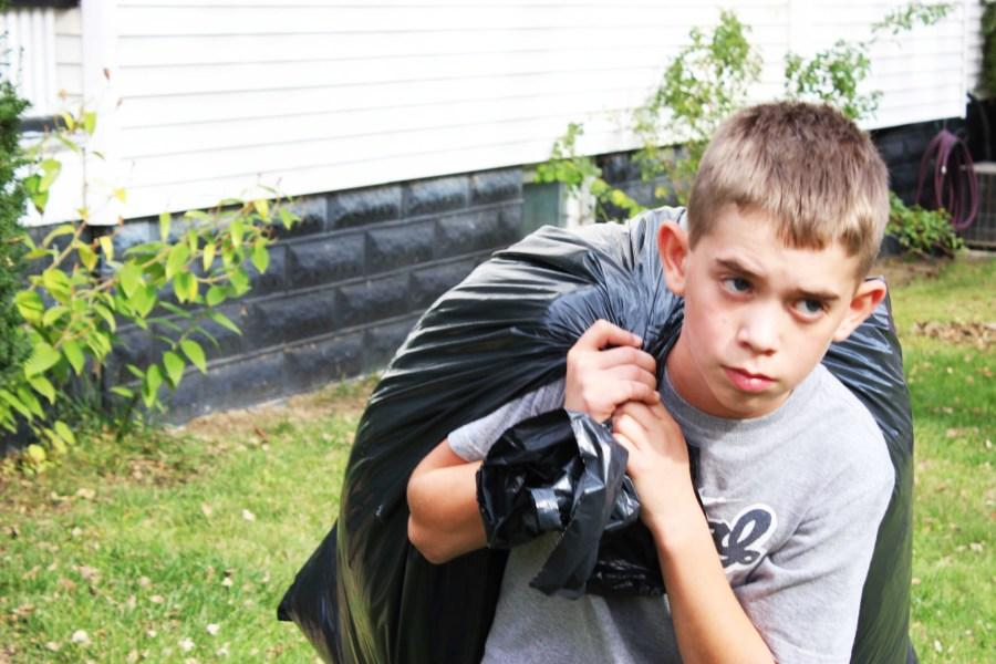 Seventh+grader+Kaden+S.+hauls+a+bag+of+leaves+to+his+fellow+classmates.+