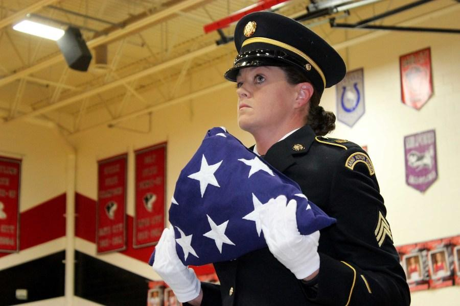 National+Guard+member+Patti+Lee+presents+the+American+flag+after+it+is+folded+13+times+symbolizing+various+virtues+and+beliefs+of+United+States+soldiers+and+veterans.