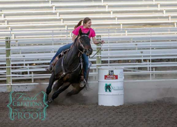 Setting her personal best time at the Madison barrel racing arena, junior Katie R. dashes past her second barrel. Katie has been barrel racing since the seventh grade along with her friend junior Abby E.