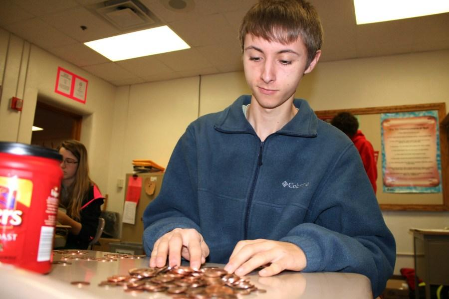 Senior+calculus+student+Dustin+D.+helps+count+money+donated+to+Make-A-Wish.+The+senior+class+ended+up+winning+the+annual+Student+Council+penny+wars+by+over+1%2C100+points.