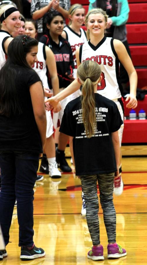 After+running+through+the+tunnel+of+varsity+players%2C+Bellwood+fifth+grader+Lili+E.++meets+senior+Hope+R.+on+the+court.+Each+elementary+girl+gets+to+choose+one+varsity+player+to+meet+on+the+court.+