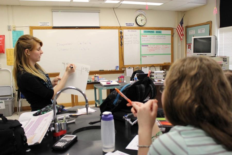 Student+Teacher+Nicole+Phelps+demonstrates+how+to+use+a+railroad+track+for+conversion+in+chemistry+to+junior+Trisha+H.+Phelps+is+temporarily+taking+over+Sander%E2%80%99s+three+chemistry+classes.