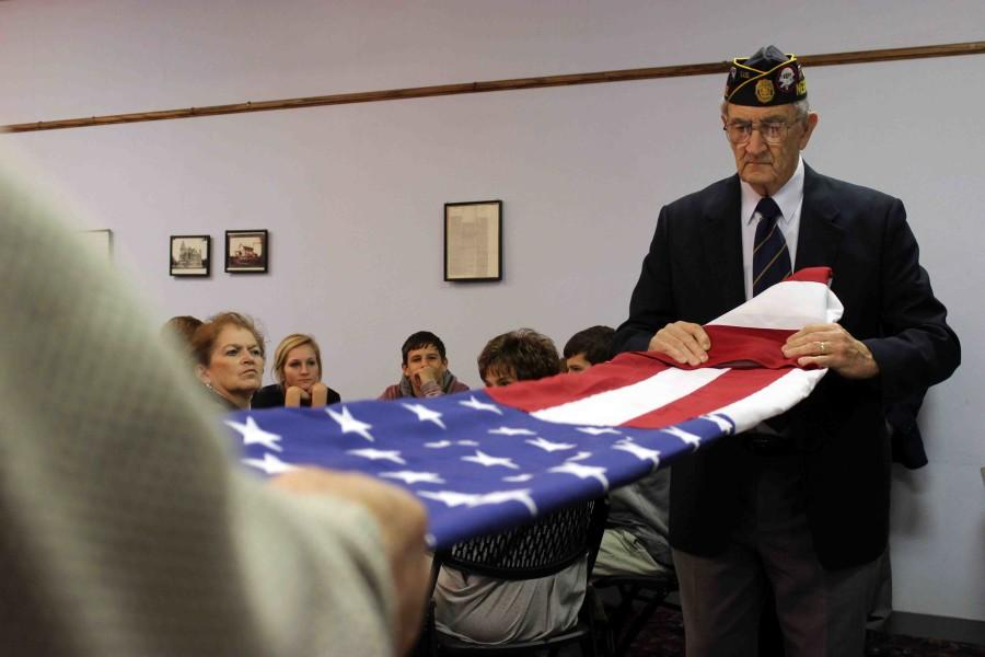 Veteran Dale Cooper begins the flag-folding demonstration held at Winfields in David City. A lunch buffet including pizza and desserts followed the presentation.
