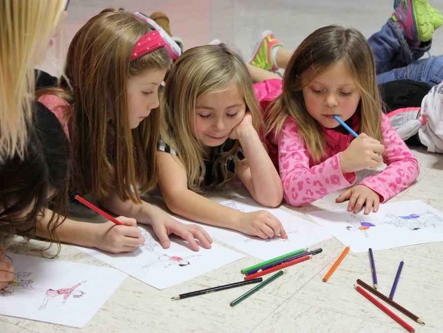 While waiting for the Bellwood students to arrive, the kindergarten and first grade students look at each others coloring to compare what they have done. Along with coloring, cheers were implemented at the beginning of each practice to help pass the time and not overwhelm the kids with their performance dance.