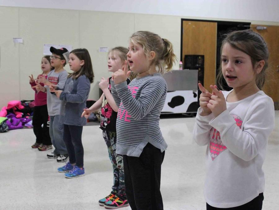 """Kindergarteners work on the cheer """"Bang, Bang Choo Choo Train,"""" led by junior Brandy Barlean and seniors Nicole Buntgen and Natalie Kirby. Along with learning dances throughout the week, the spirit squads made sure the kids worked on cheers as well."""