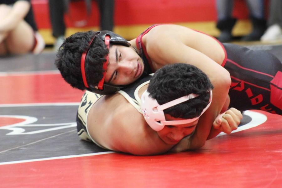 Looking+for+a+pin%2C+senior+Lester+Palencia+holds+control+over+Aquinas+wrestler+Carlos+Chavez.+Palencia+won+both+of+his+matches+that+night+by+pin.