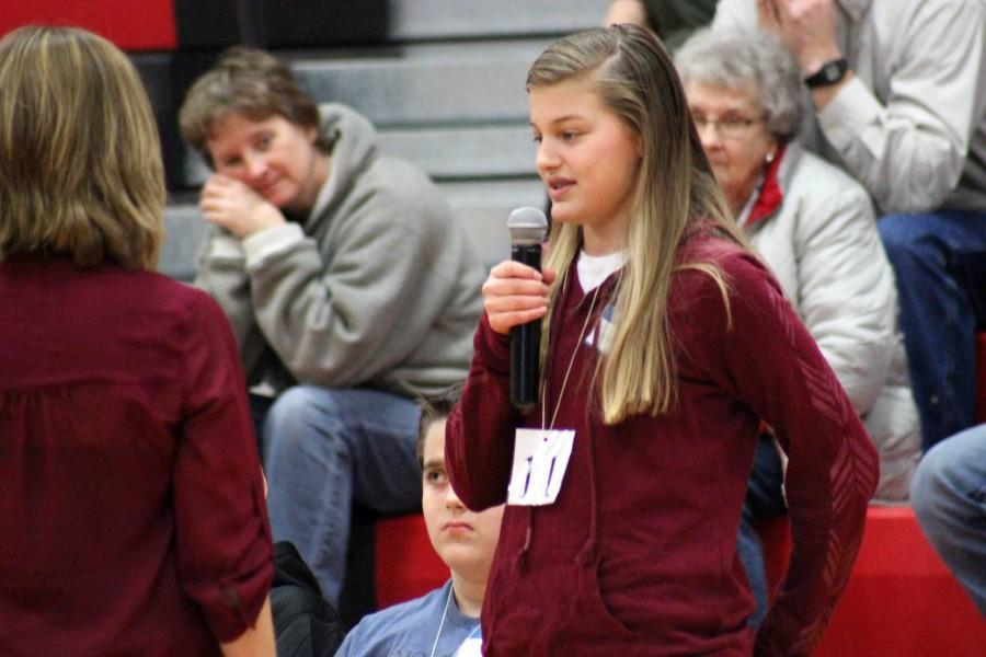 Taking her turn at the microphone, seventh grader Payton Andel spells her first name to Bales. Finalists were told to practice spelling their names so they can get a better feel of the process of the competition.