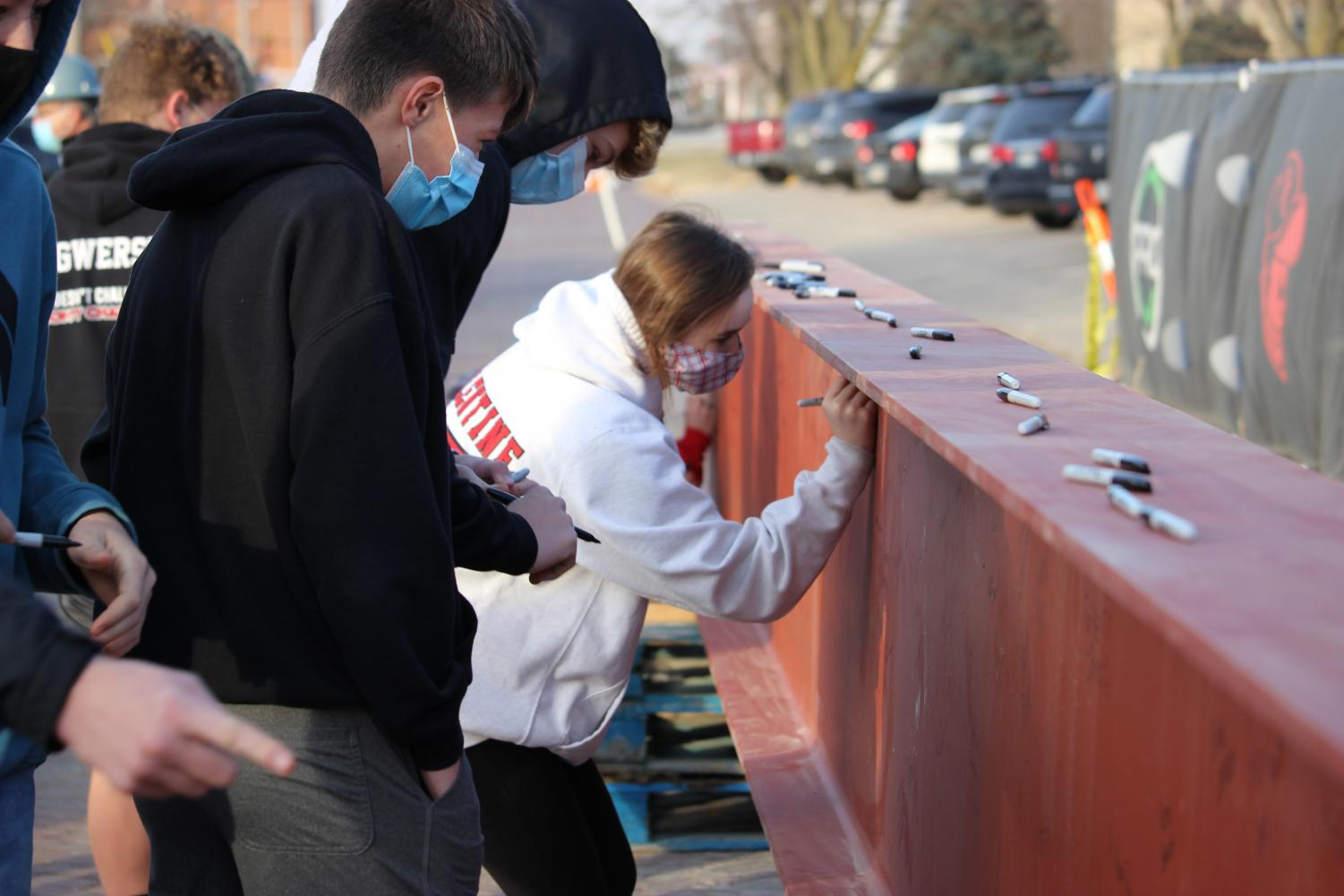 DCHS students sign their names on the final beam of the school